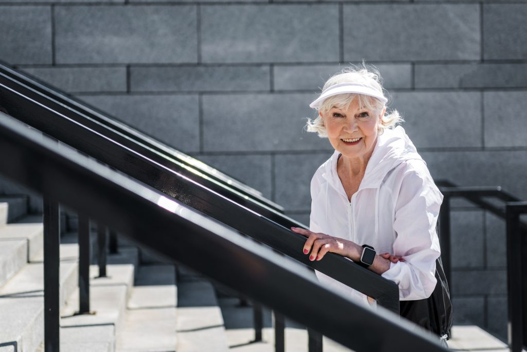 senior woman walking up an outdoor staircase
